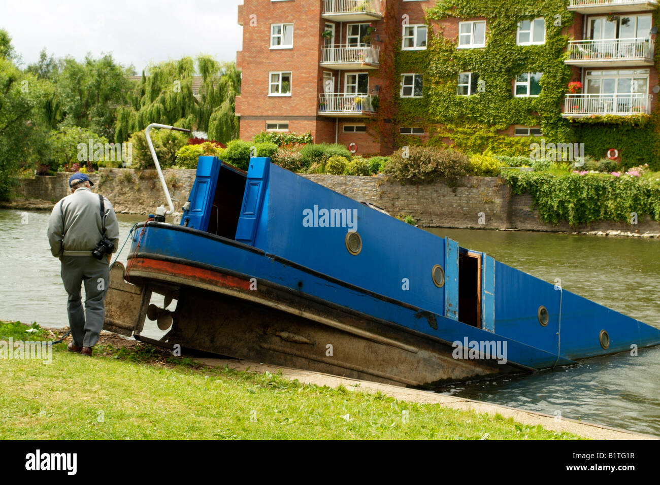 Man inspects a canalboat sinking into the River Avon at Stratford upon Avon England UK - Stock Image