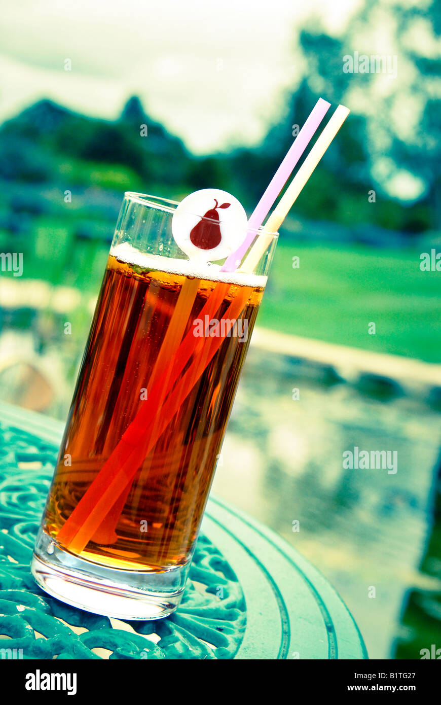 A glass of Pimms and lemonade on a table at a wedding reception.  The background is cross-processed - Stock Image