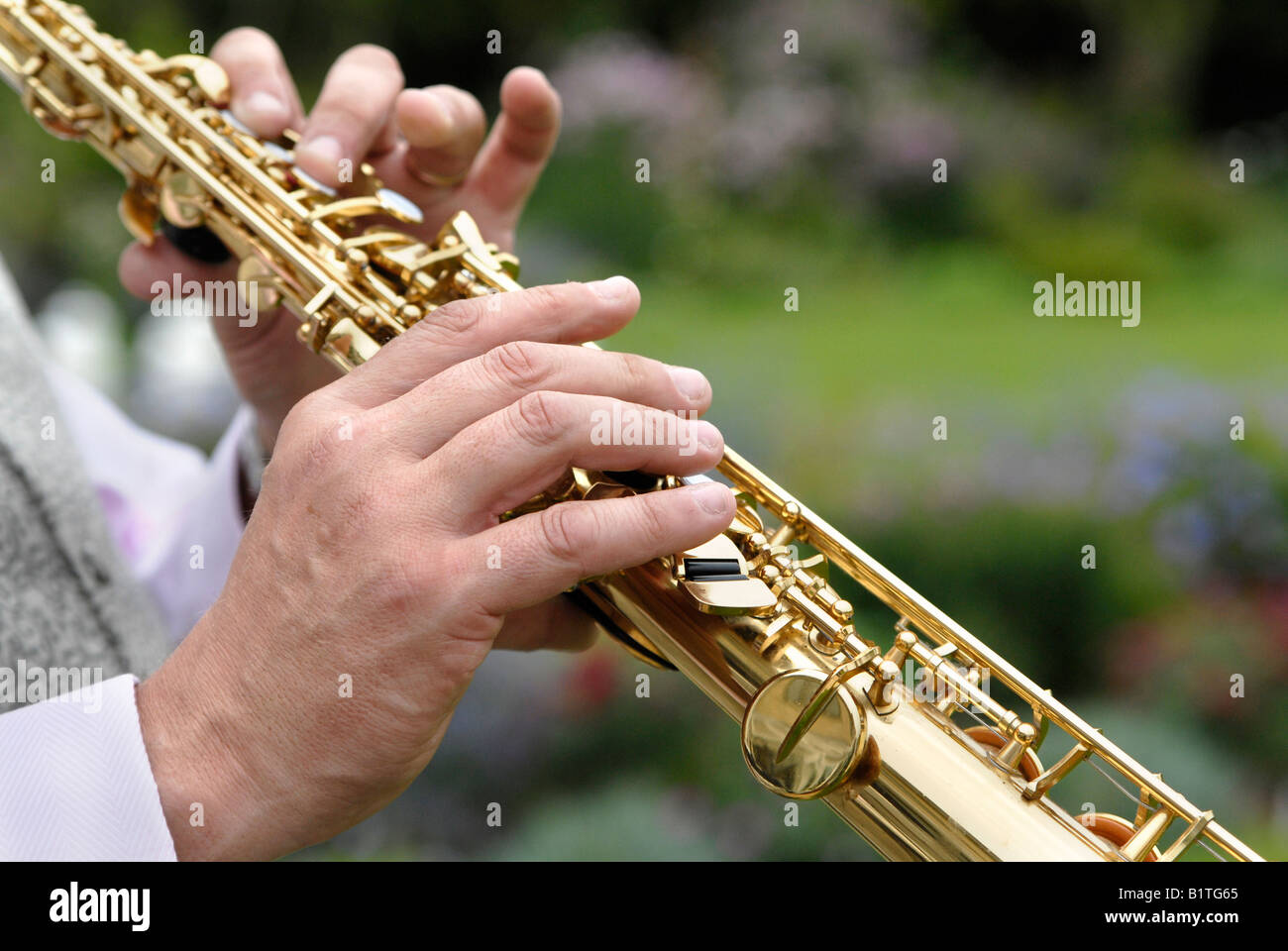 A saxophonist playing for the guests, in a hotel garden, at