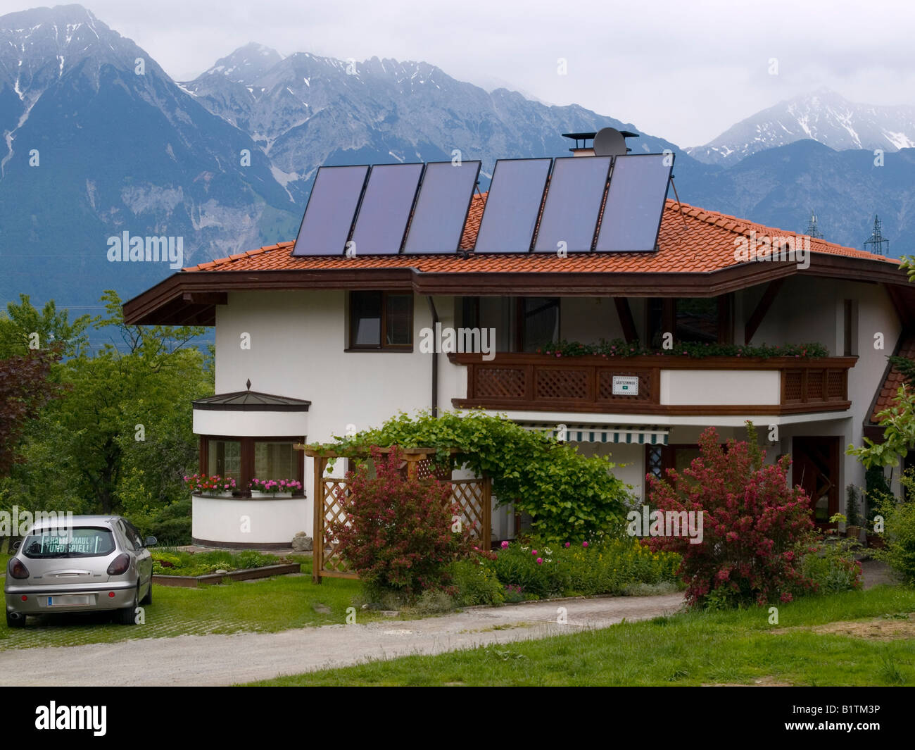 A house fitted with an array of solar panels for water heating in Lans Innsbruck Austria - Stock Image