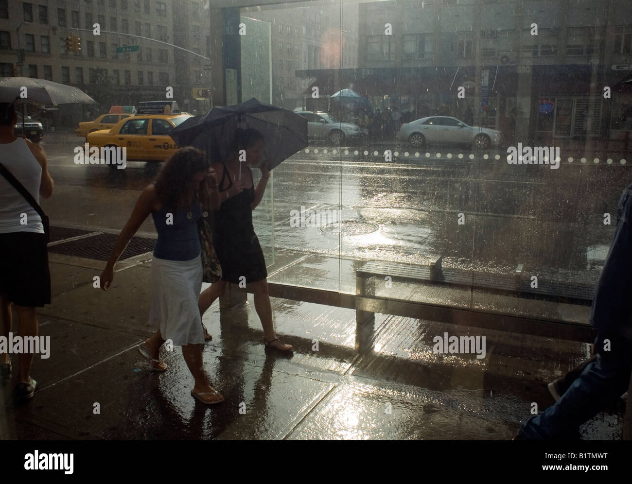 Pedestrians in the New York neighborhood of Chelsea endure a drenching rainstorm - Stock Image