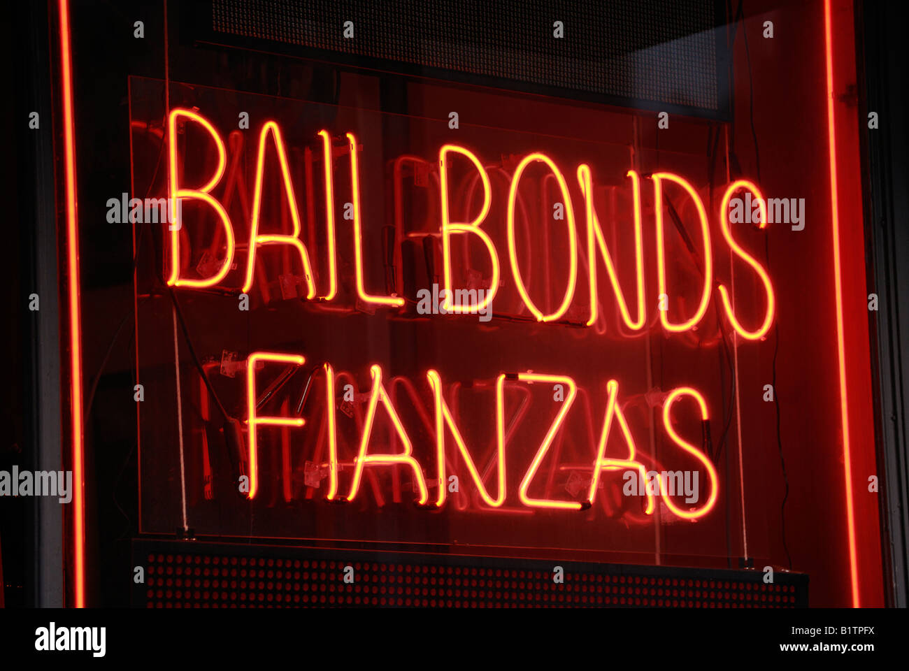 Neon sign in the window of a bail bonds company near the courts in Lower Manhattan advertises in both English and - Stock Image