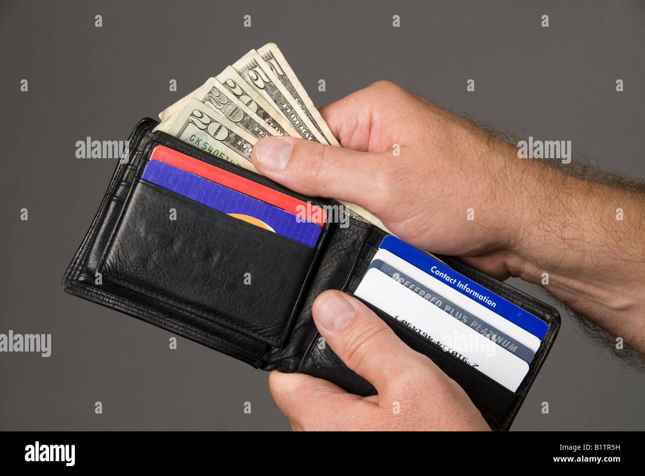 Dishing out cash from a leather wallet to pay bills - Stock Image