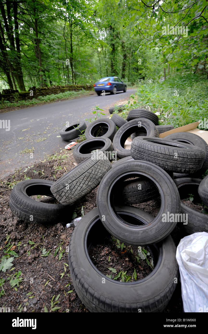 Illegally dumped Tyres left by fly-tippers at the side of a country lane in the Cotswolds. Picture by Jim Holden. - Stock Image