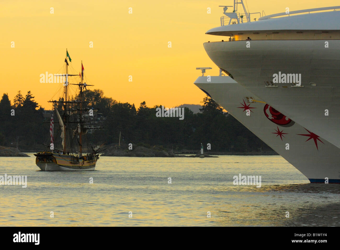 Docked cruise ships and Lady Washington tall ship entering harbour at sunset-Victoria, British Columbia, Canada. - Stock Image