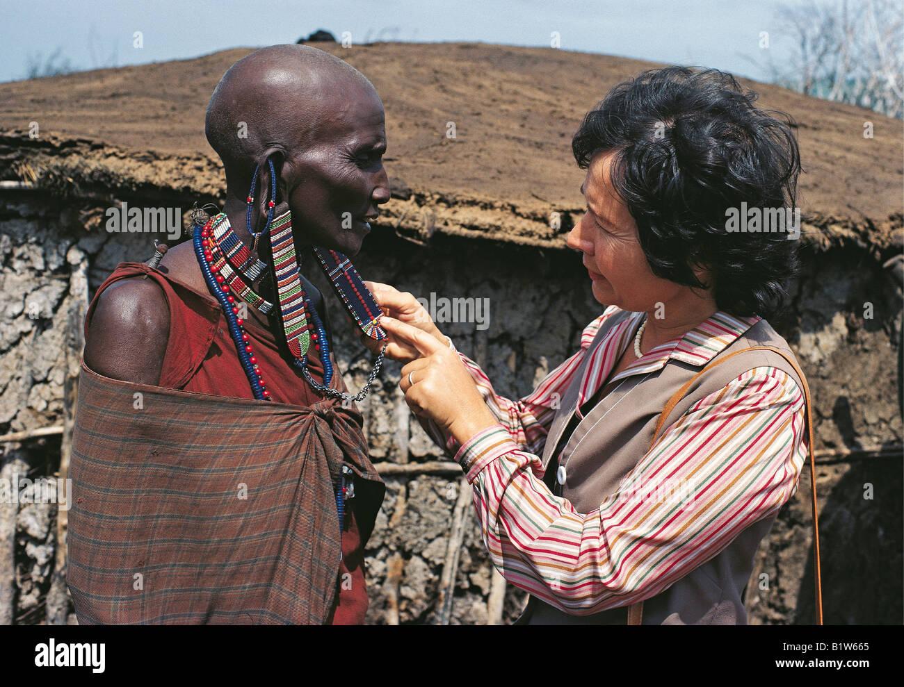 White lady tourist caucasian admiring Maasai woman s ear ornaments Masai Mara National Reserve Kenya East Africa - Stock Image