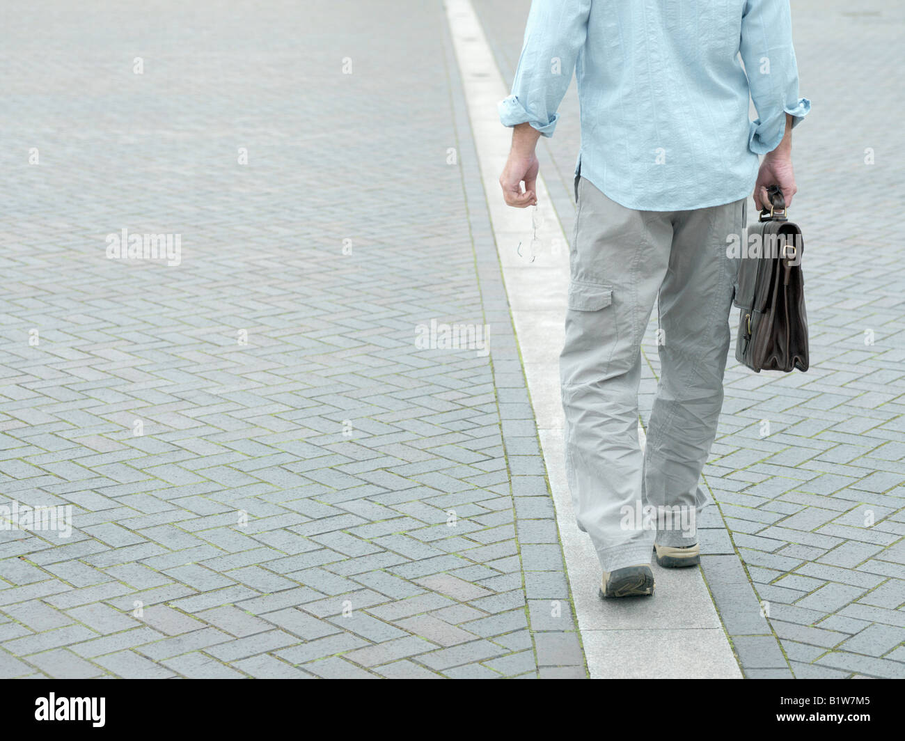 man walking along white line Stock Photo