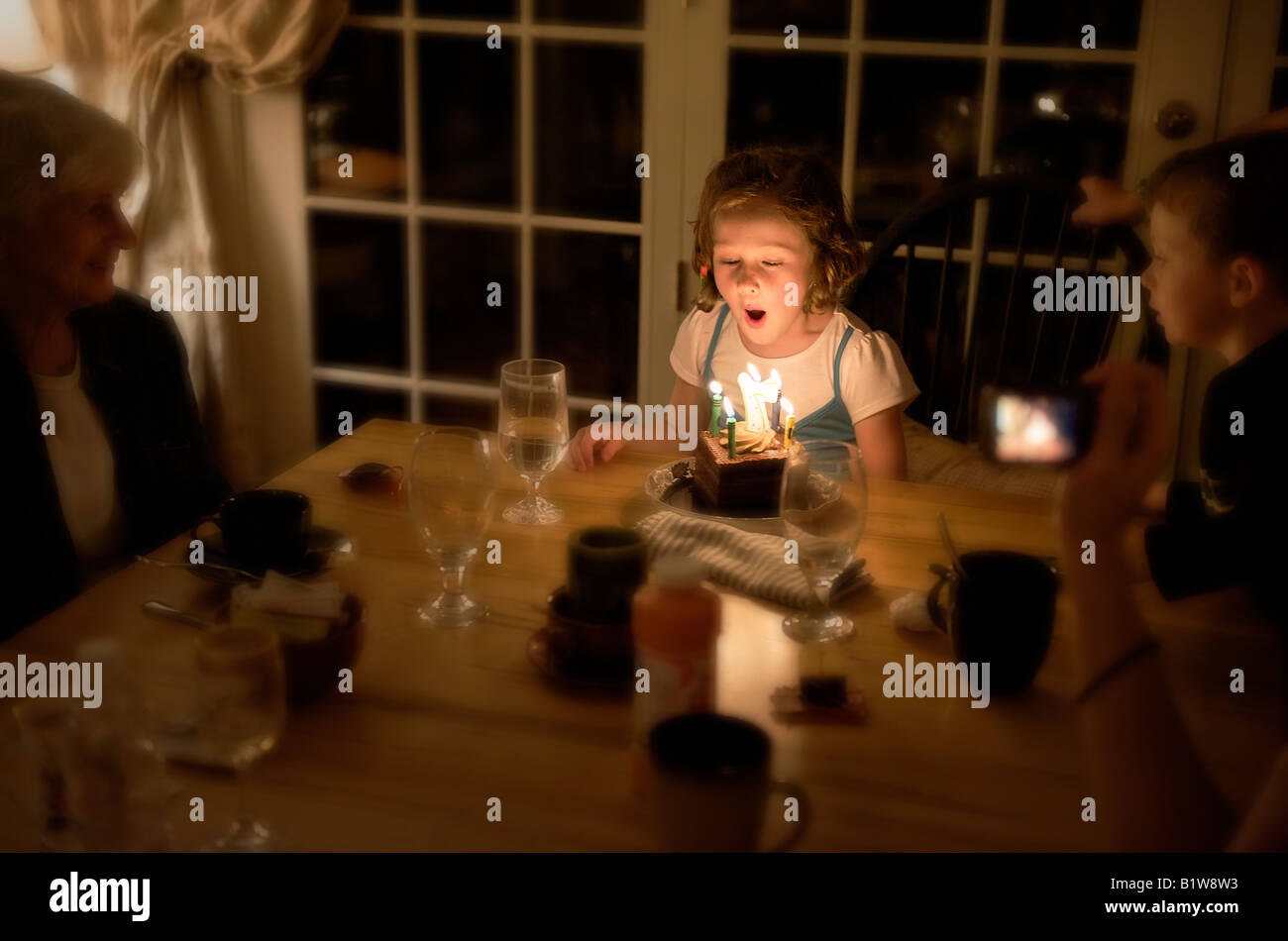 Seven year old girl blows out the candles on her birthday cake - Stock Image