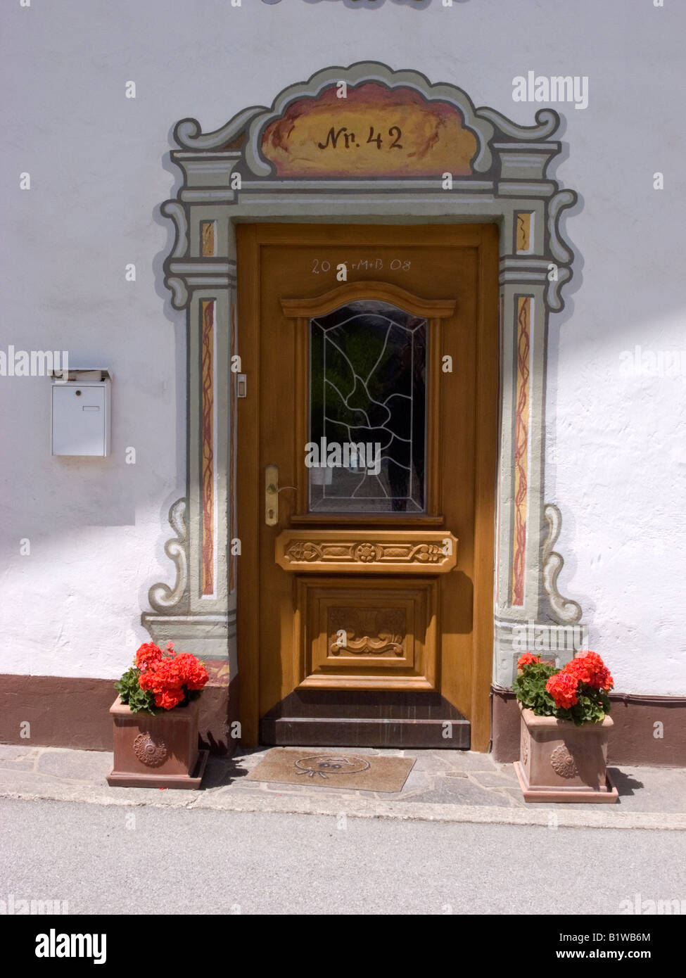 Front door with traditional hand painted decorative surround and pots of geraniums in Sistrans Innsbruck Tirol Austria Stock Photo