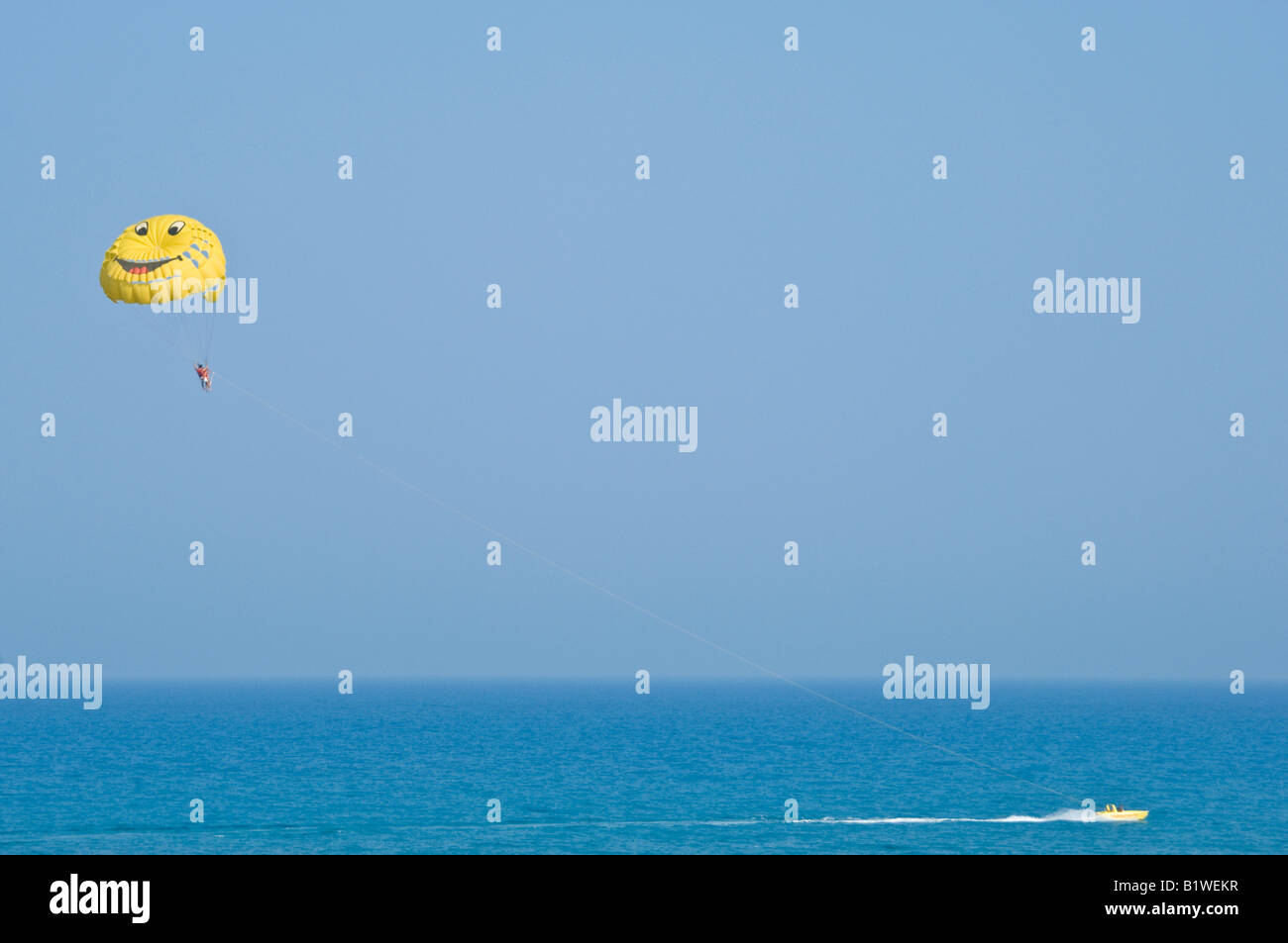 A wide angle view of parasailing near Hammamet in Tunisia on a sunny day against a bright blue sky. - Stock Image