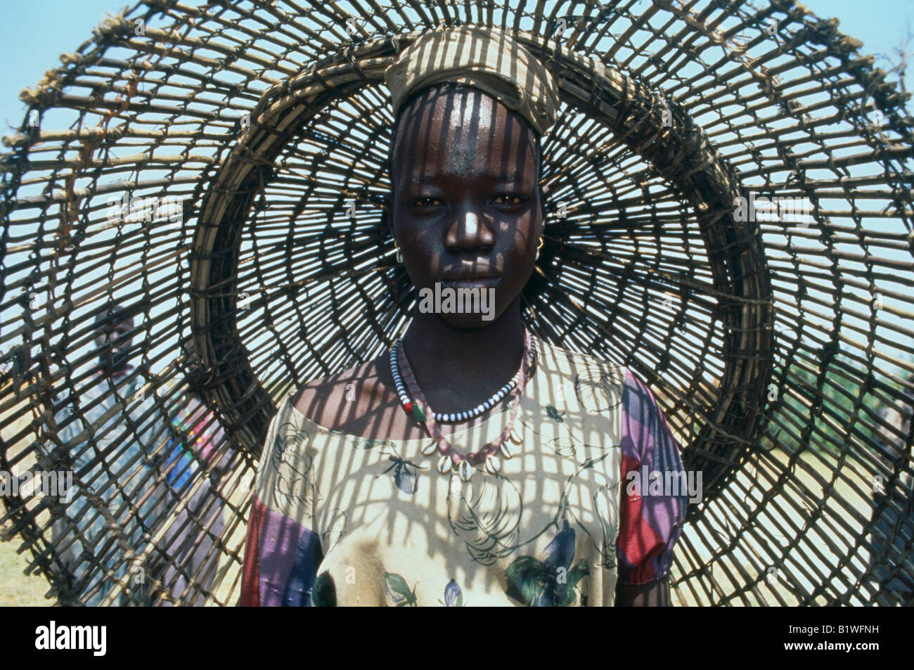 SUDAN North Africa Bahr el Ghazal Portrait of young Dinka woman with fishing basket behind her casting shadow pattern - Stock Image