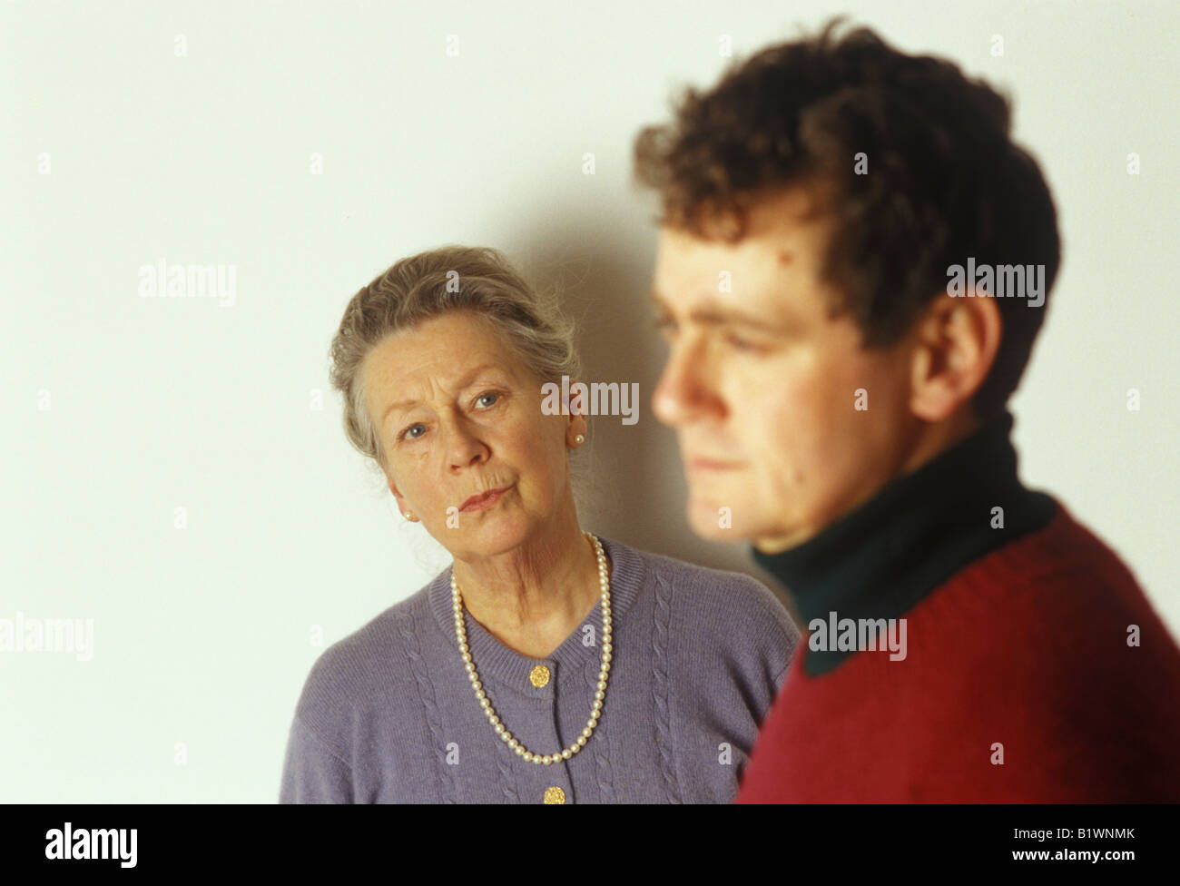 older woman looking worried at younger man - Stock Image