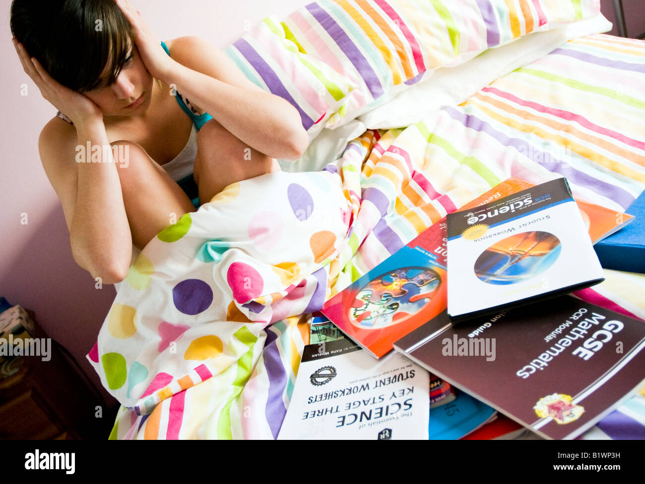 teenage girl in bed with GCSE revision books around her looking anxious - Stock Image