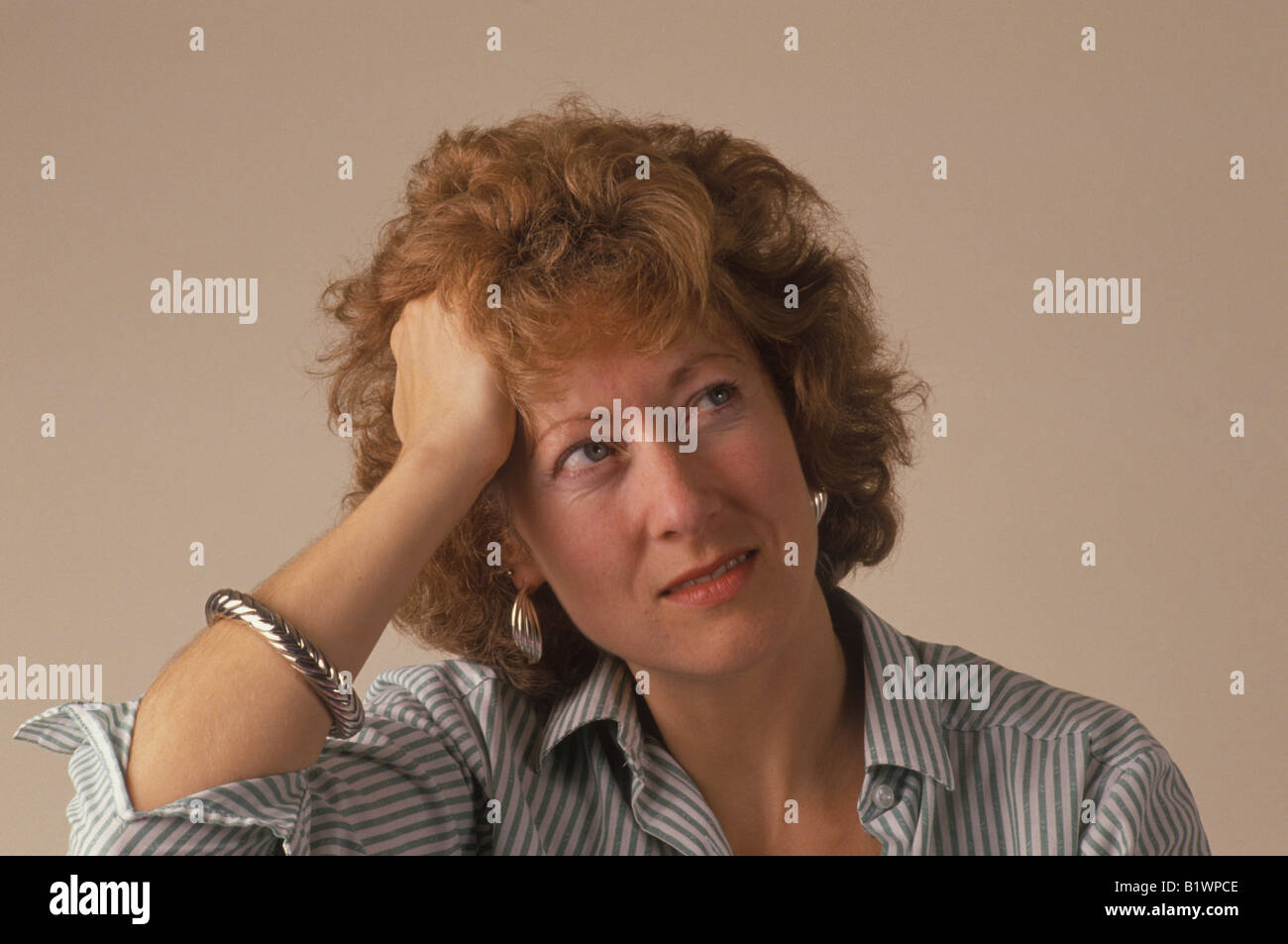 stressed woman holding her head - Stock Image