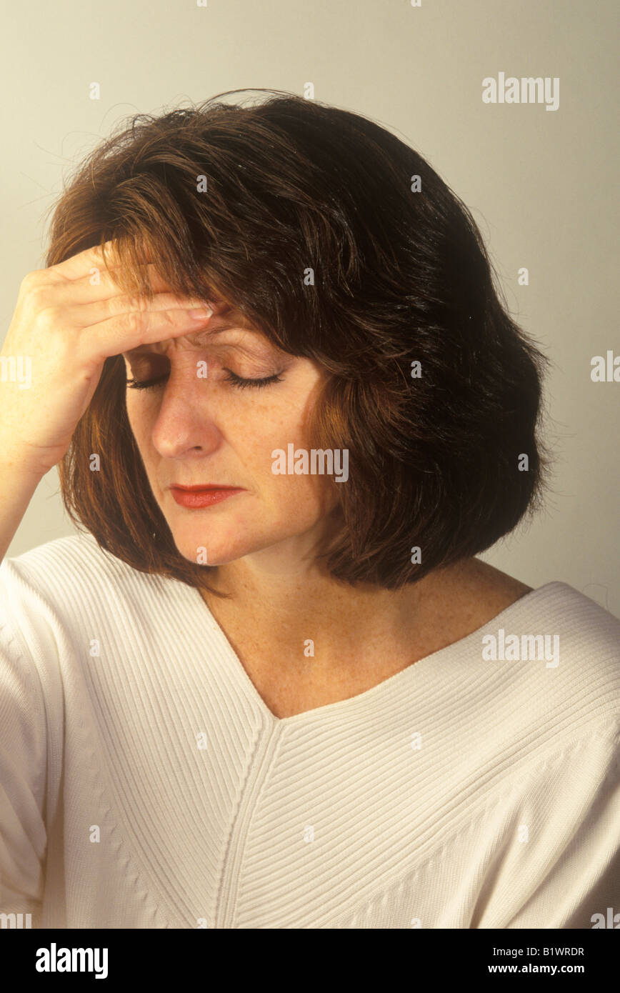woman with her hand to her head looking unhappy - Stock Image