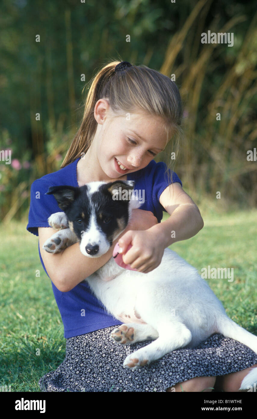 little girl playing with a puppy in the garden - Stock Image