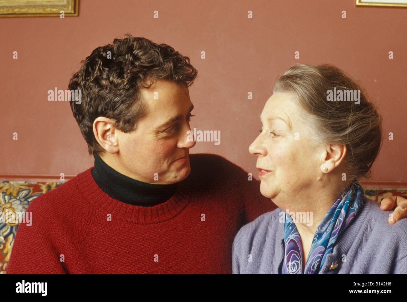 younger man looking at an older woman - Stock Image