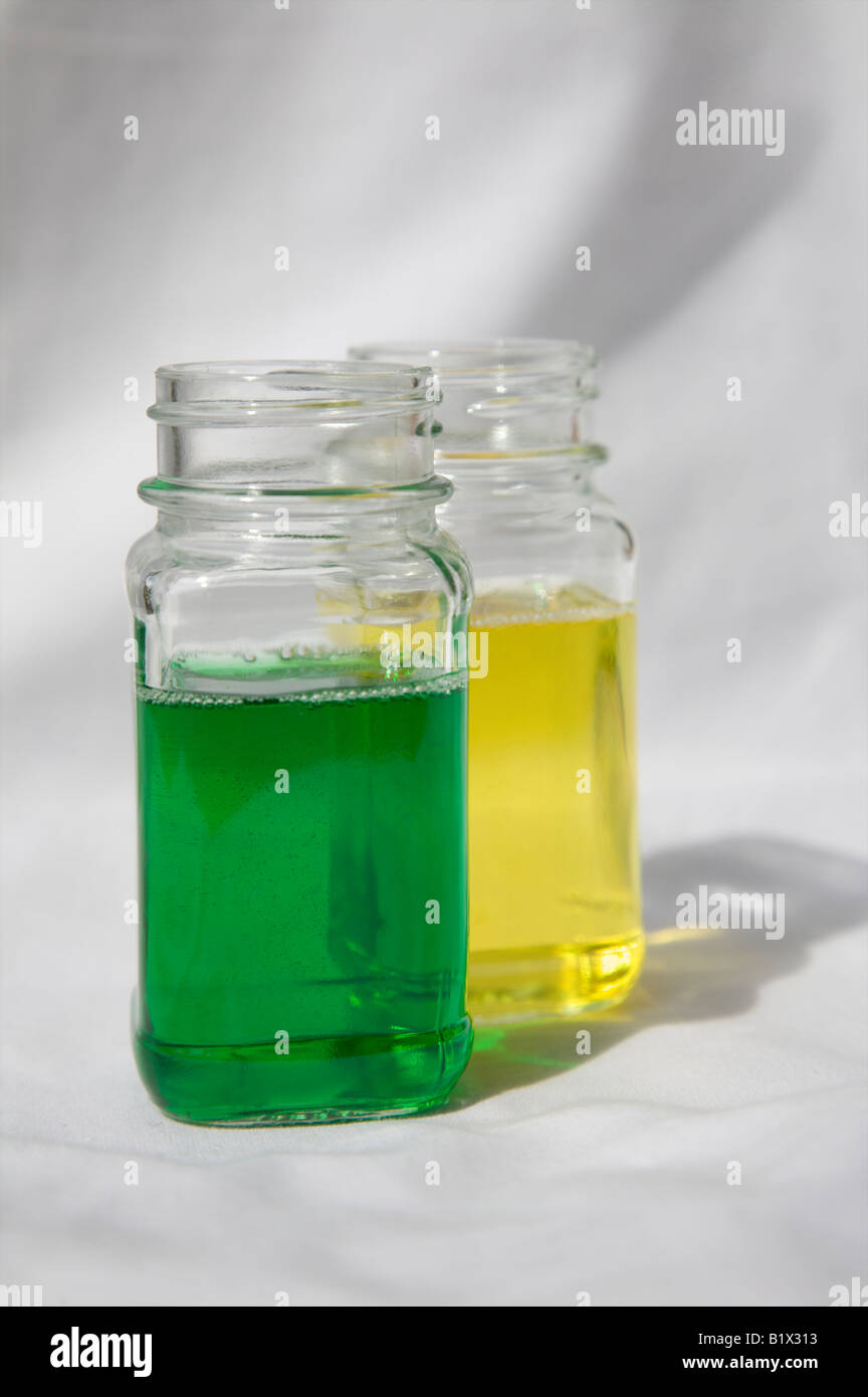 OPEN GLASS BOTTLES CONTAINING GREEN AND YELLOW LIQUID Stock