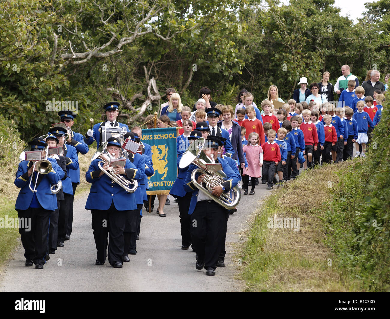 Bude town band leading children from St. Marks school to church for the Patronal festival, at crosstown. - Stock Image
