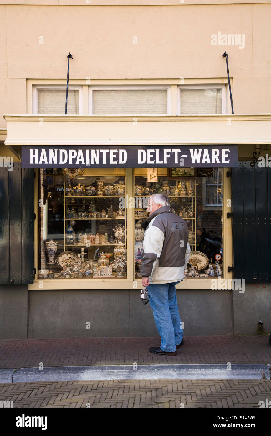 Passer by looks at Royal Delftware pottery on display in a shop window in Delft. Netherlands. - Stock Image