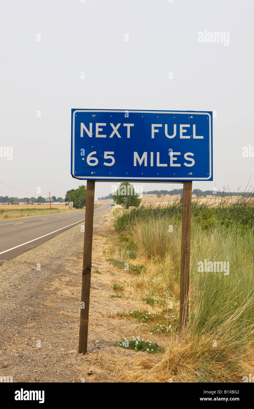 Highway road sign that reads 'Next Fuel 65 Miles' near Red Bluff, California, USA. - Stock Image