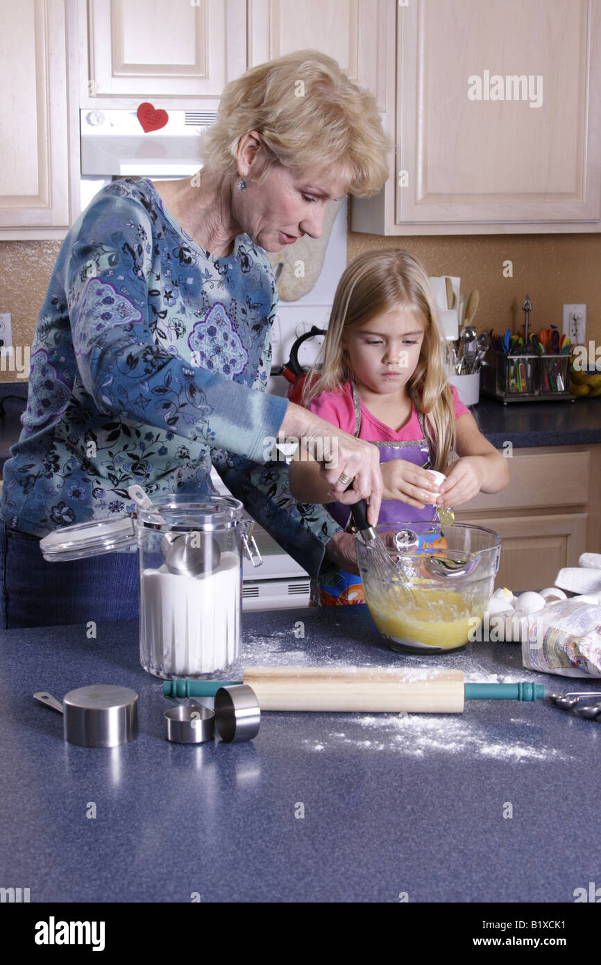 Stock Photograph of a young girl and grandmother baking - Stock Image