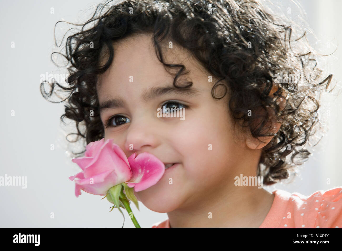 Close-up of a girl smelling a rose - Stock Image