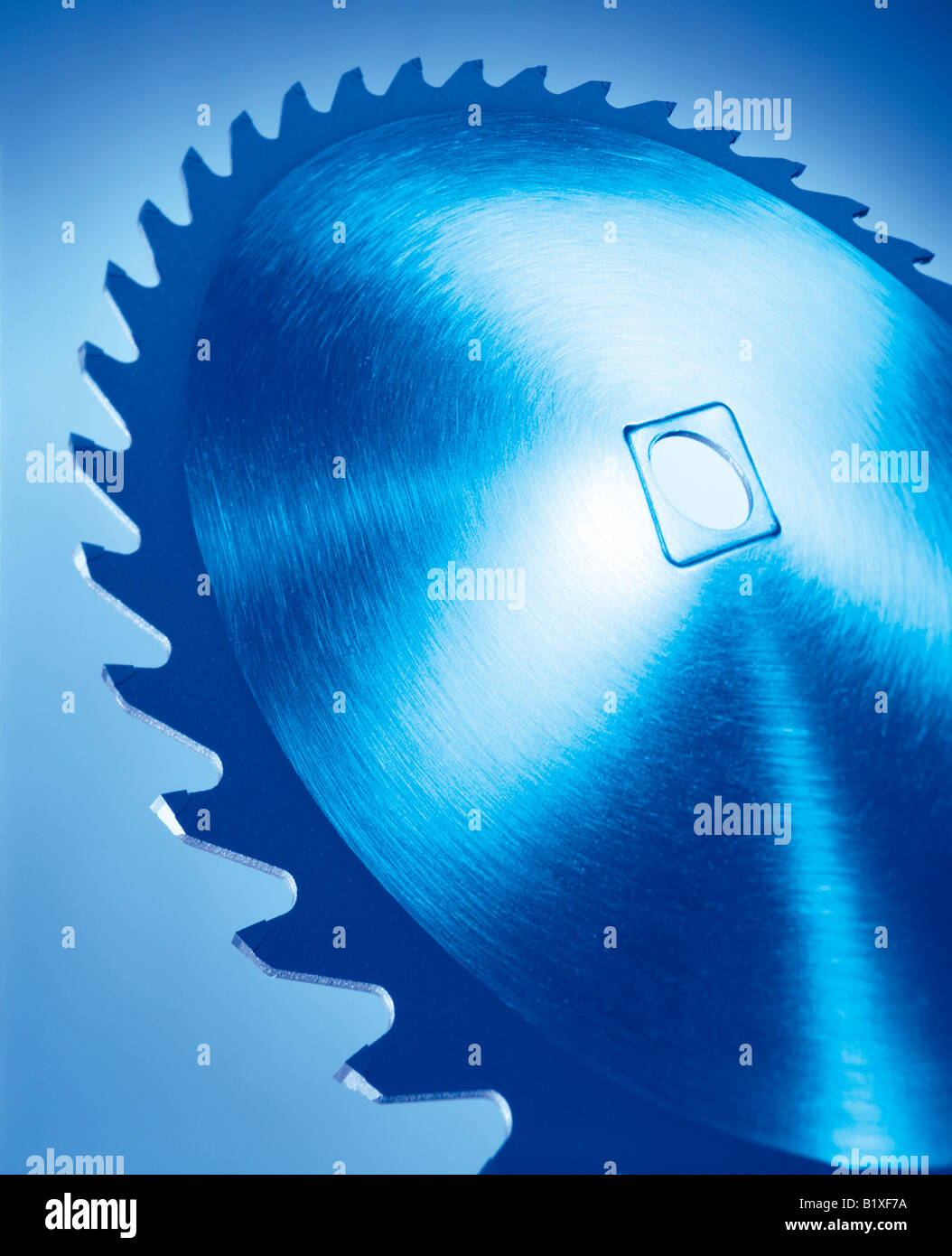 A large close up of a blue metal saw blade with large teeth - Stock Image