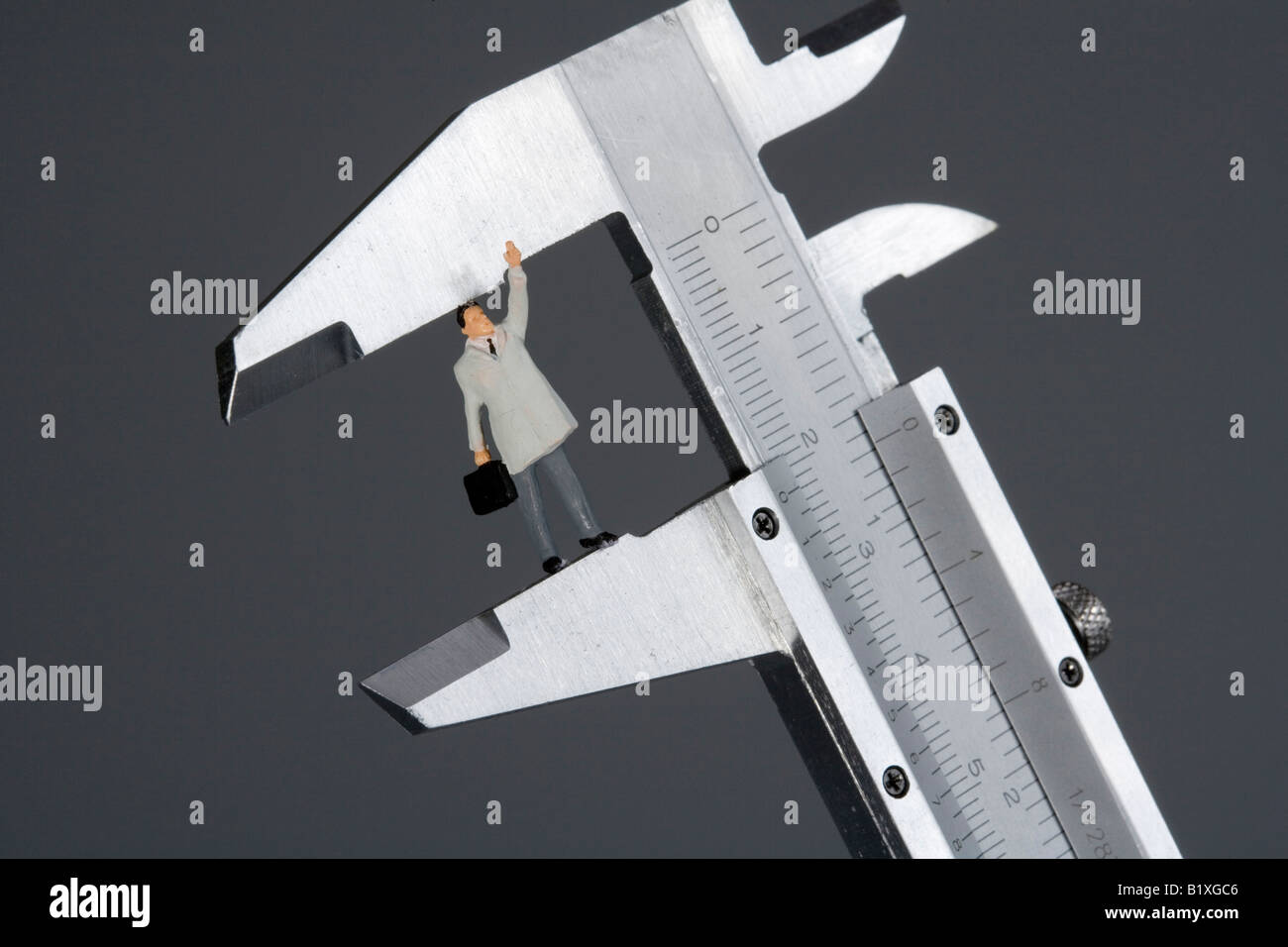 Figure of a businessman in a calliper ruler - Stock Image