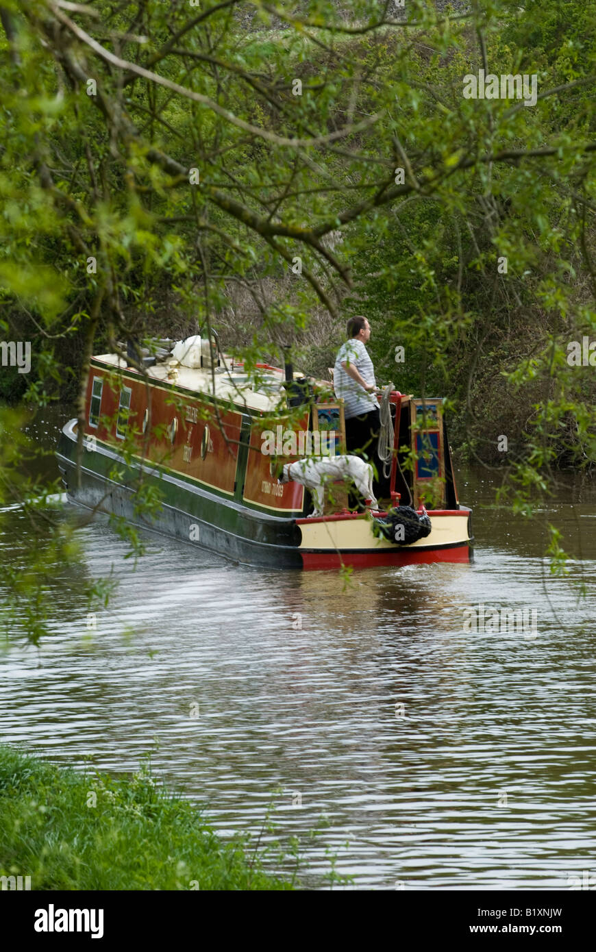 A man and his dog aboard a narrow boat on the Oxford Canal. UK - Stock Image