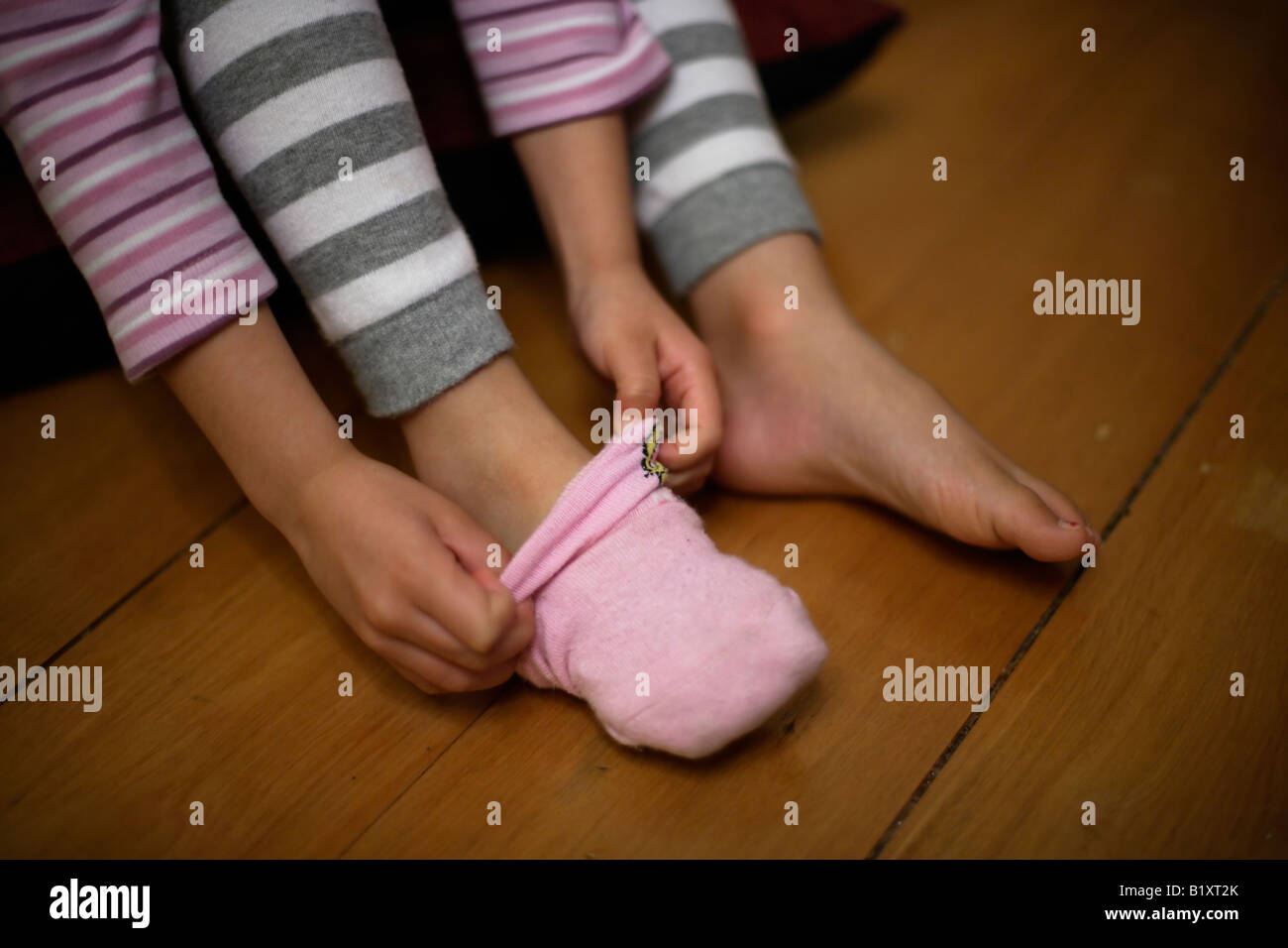 Girl aged four pulls on her pink socks - Stock Image