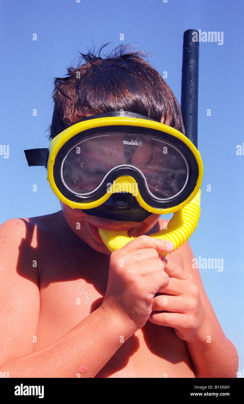 portrait of a young boy wearing diving goggles and snorkel - Stock Image