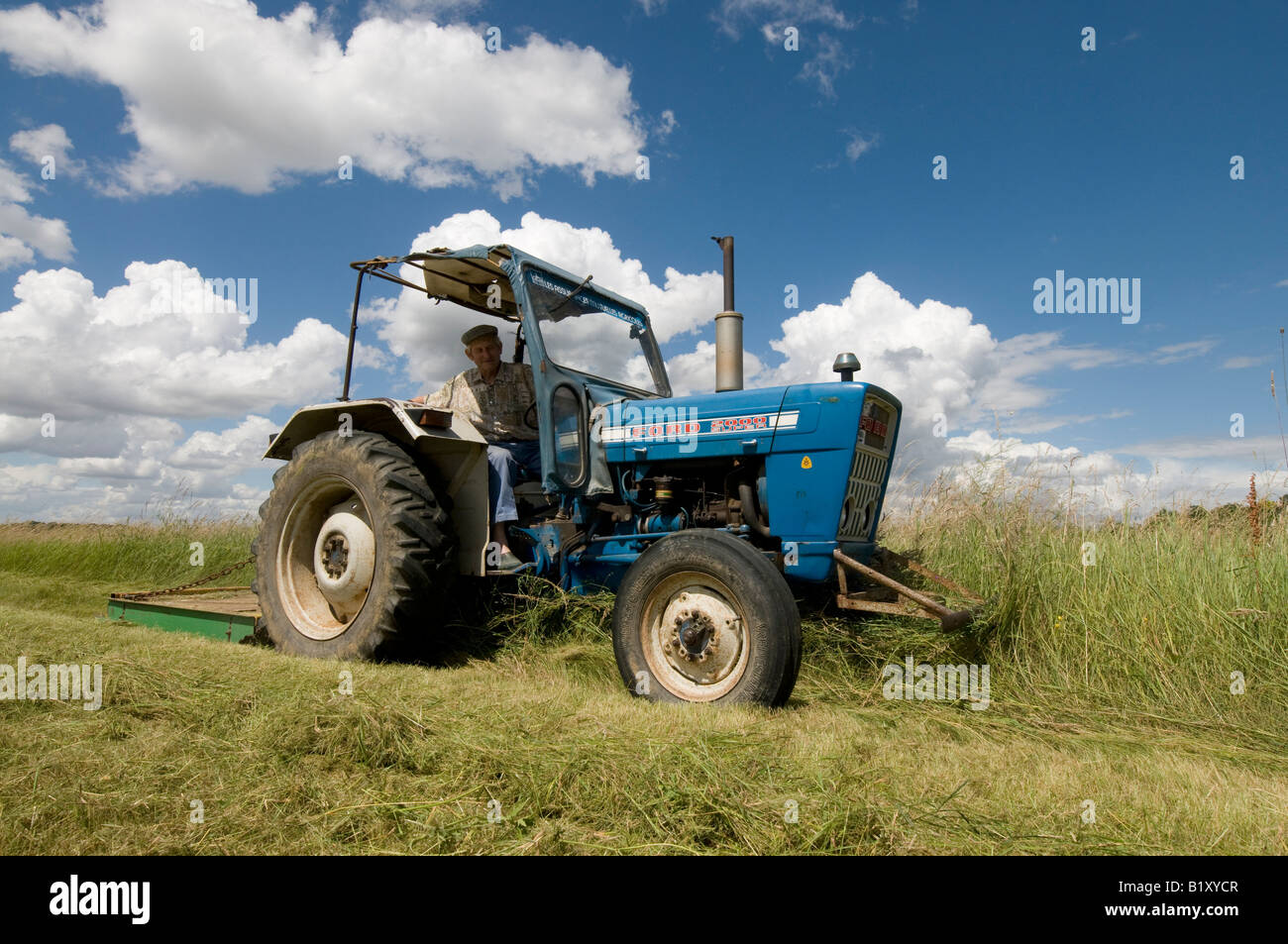 Farmer on old ford 2000 tractor cutting meadow sud touraine france