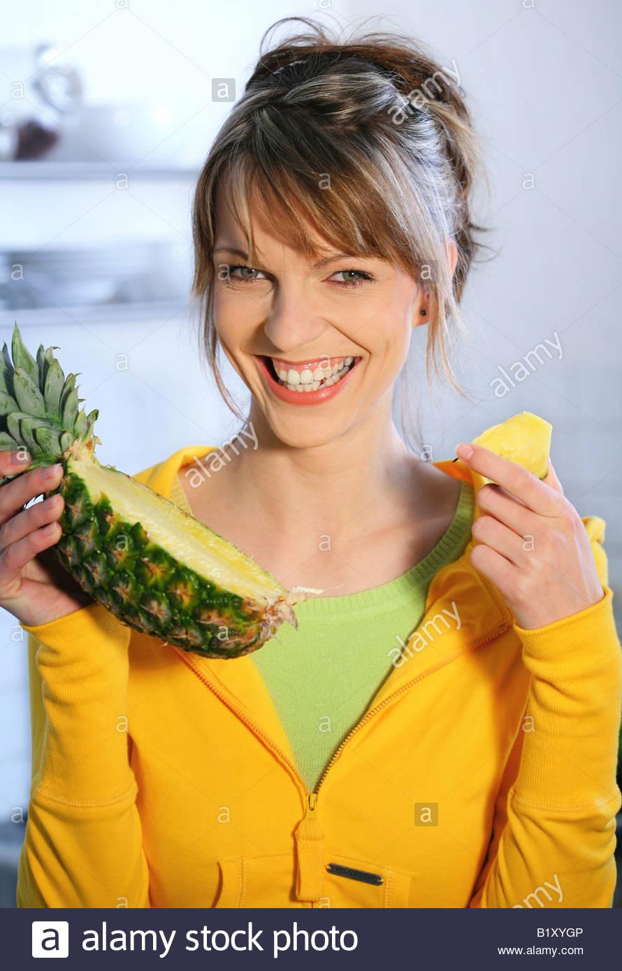 woman eating pineapple Stock Photo