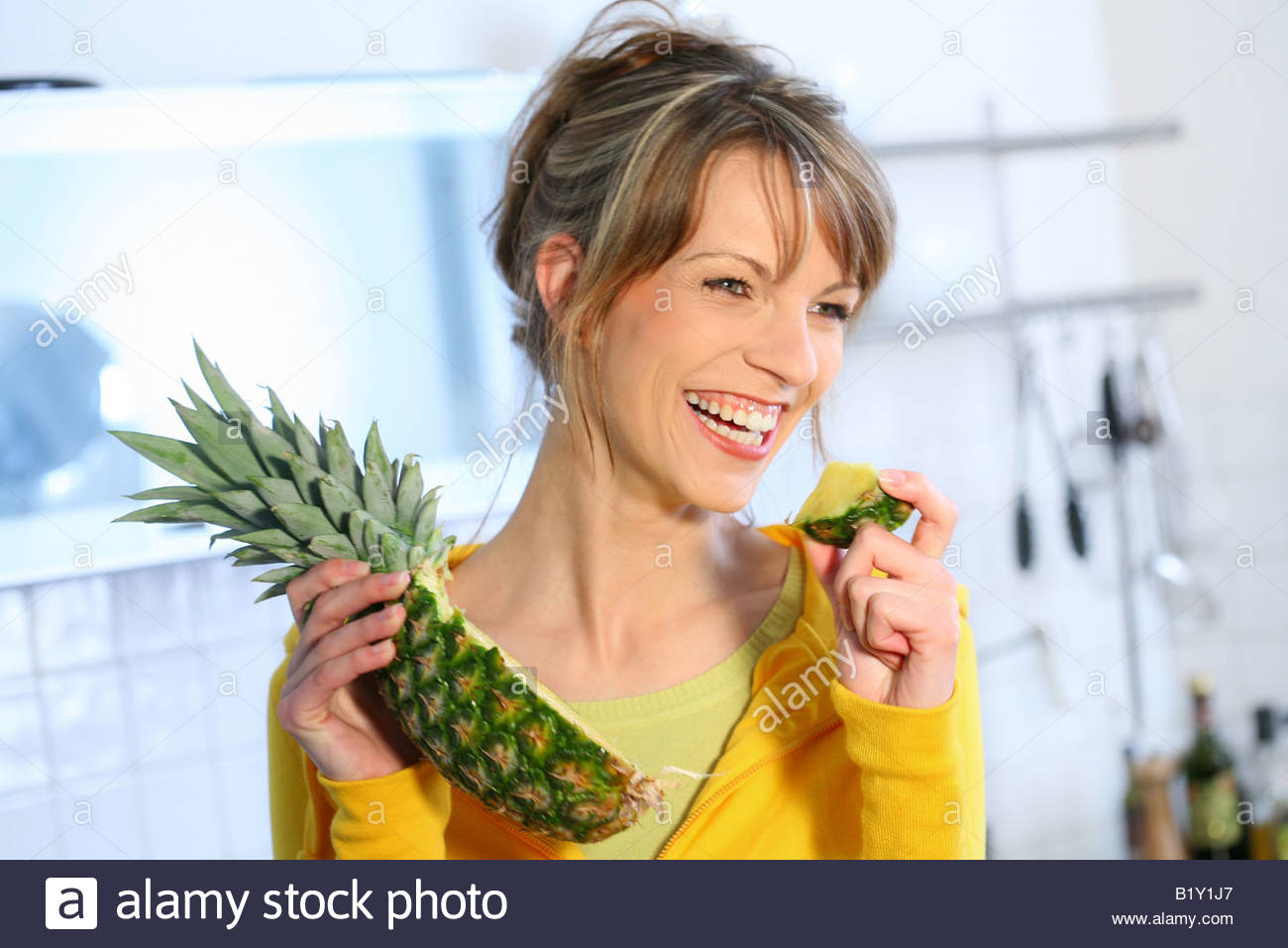 woman eating pineapple - Stock Image