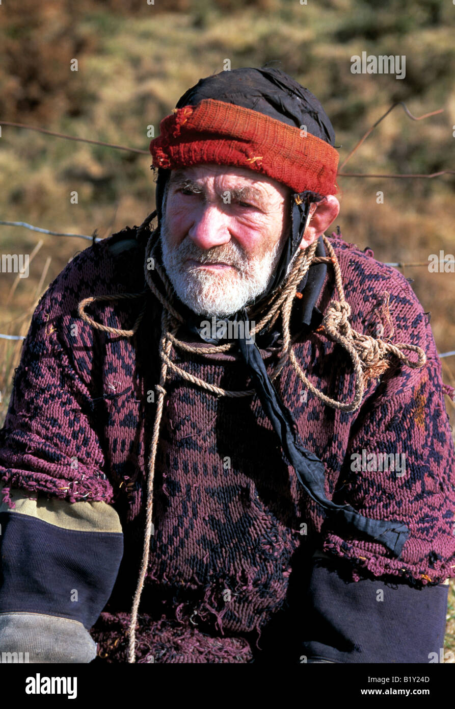 old man dressed for winter sits on a roadside fence on the ring of kerry - Stock Image