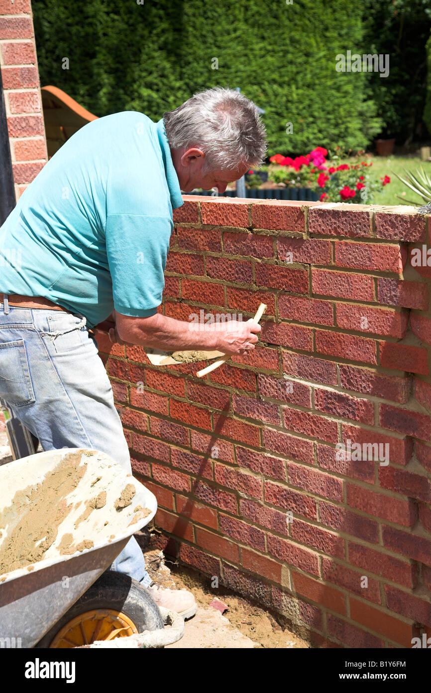 Bricklayer building a garden wall Stock Photo: 18422872 - Alamy
