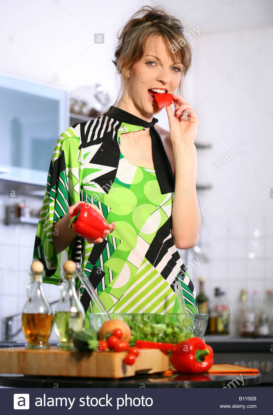 Woman eating red pepper Stock Photo