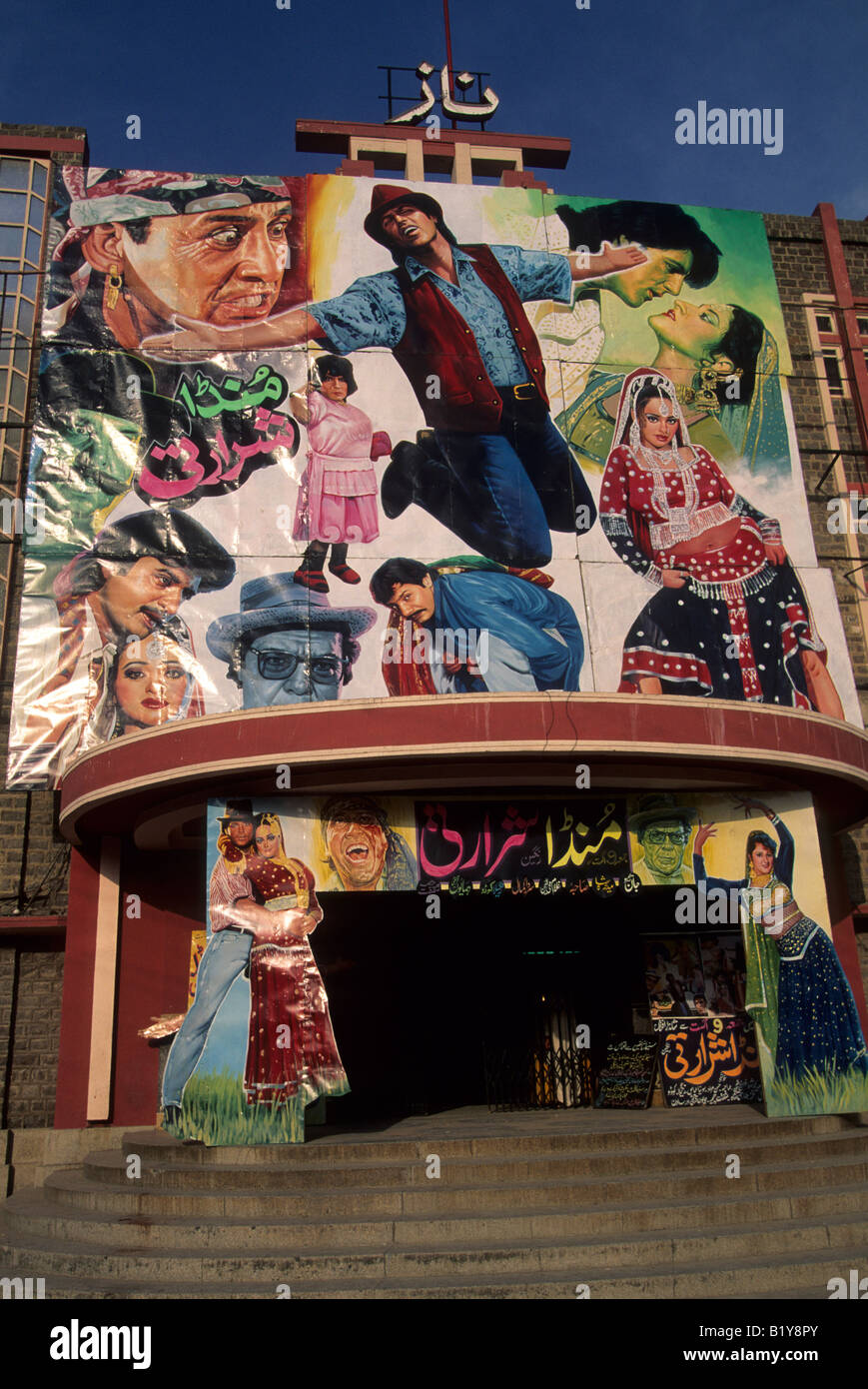 A colorful movie poster displays hand painted illustrations of it s cast above the entrance to a Rawalpindi Pakistan - Stock Image