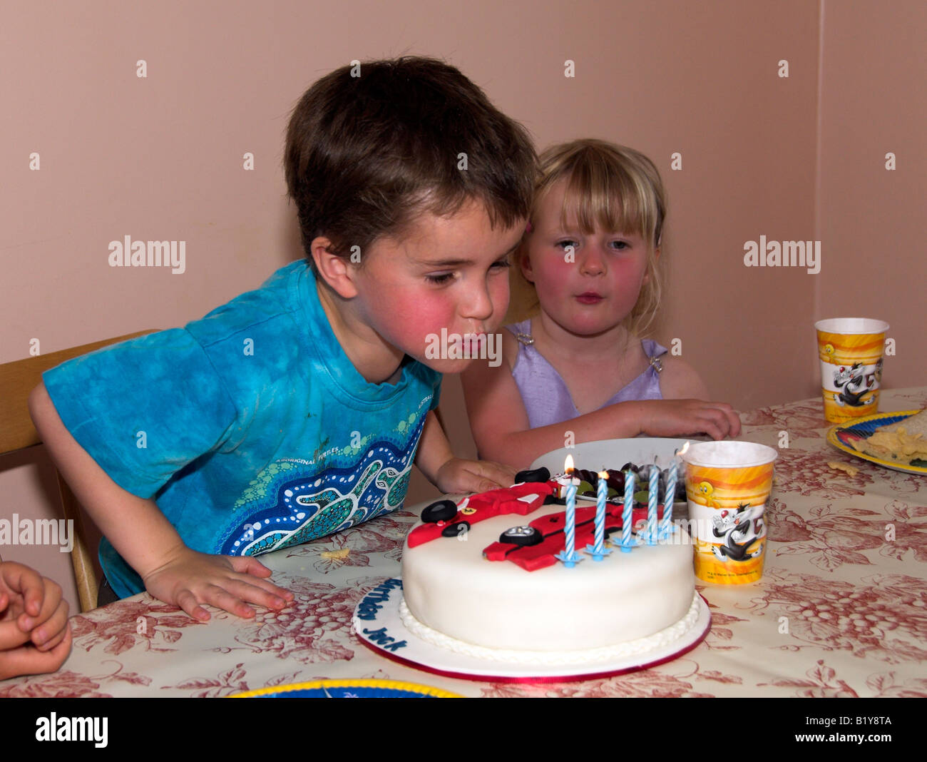 Boy Aged 5 Blowing Out Candles On A Novelty Birthday Cake