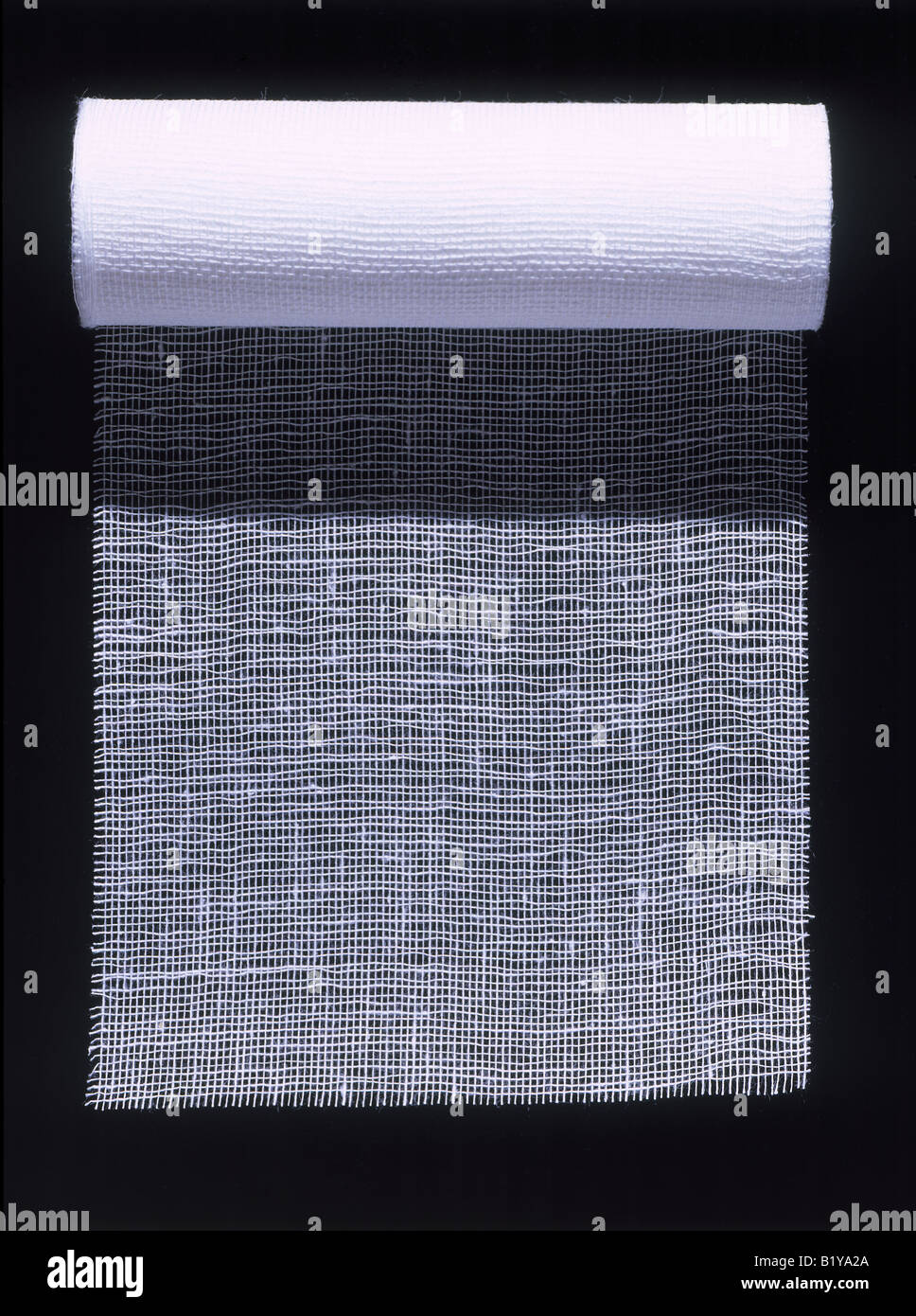 A roll of white medical gauze unrolled on black. - Stock Image