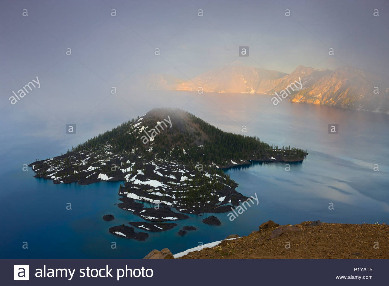 Thick fog seems to originate from the volcanic cone of Wizard Island located in Crater Lake, Oregon. - Stock Image