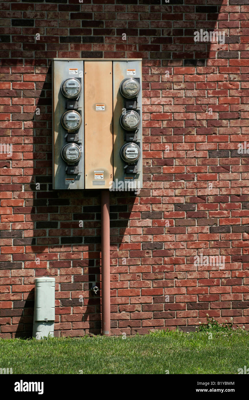 Electricity meters on the side of an apartment complex - Stock Image