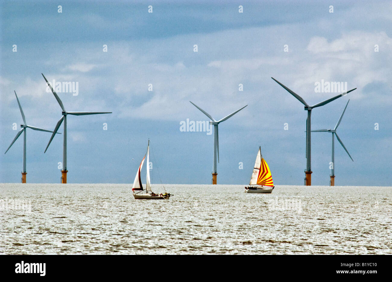 yachts-sail-by-giant-windmills-at-sea-on