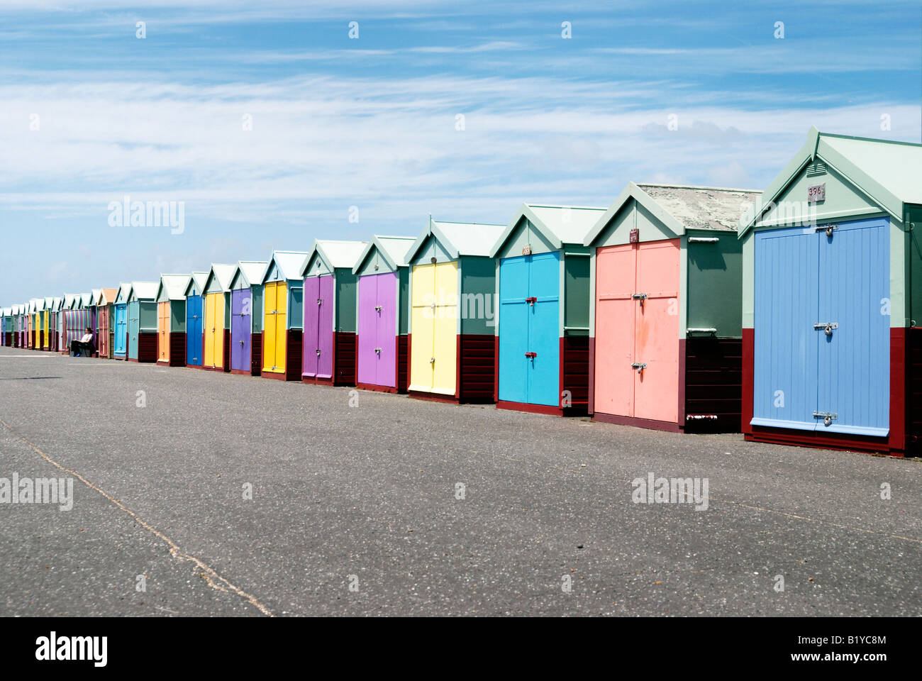 Woman sitting outside a row of colourful beachhuts on the seafront in Hove - Stock Image