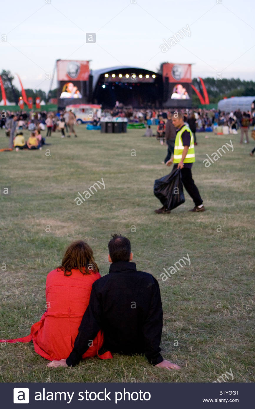 a couple sitting on the grass at the mighty boosh festival at the hop farm in kent england - Stock Image