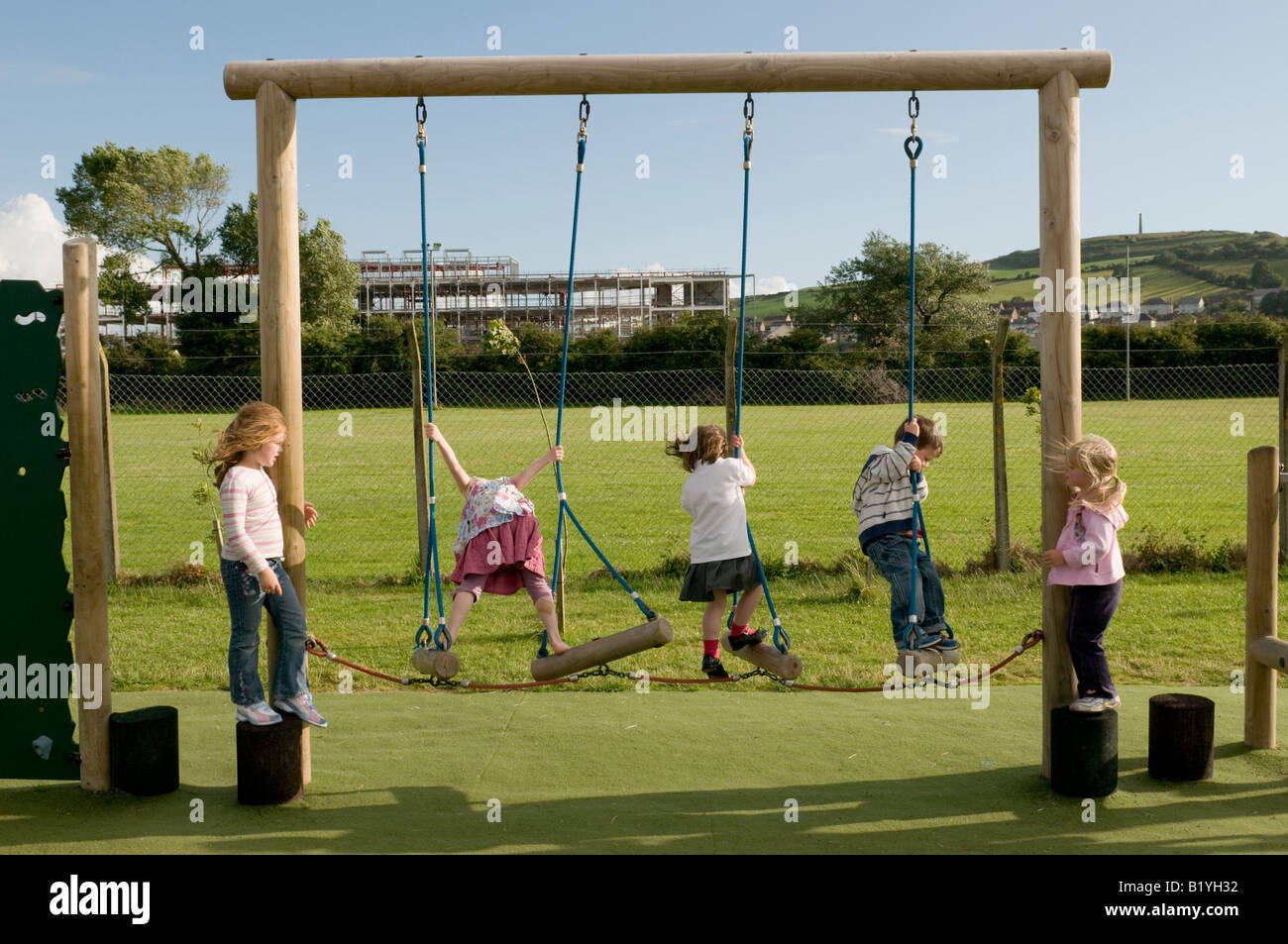 five 5 primary school children outdoors in playground playing on rope climbing exercise  frame, Aberystwyth Wales - Stock Image