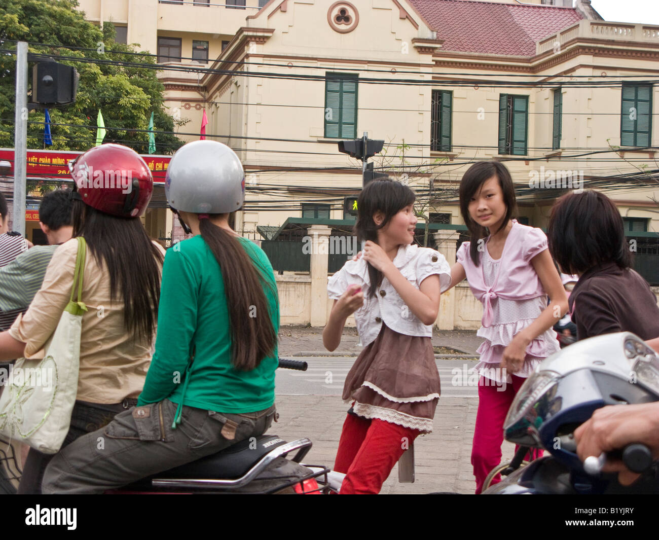 motorbike traffic and girl pedestrians in busy street in Hanoi, Vietnam - Stock Image