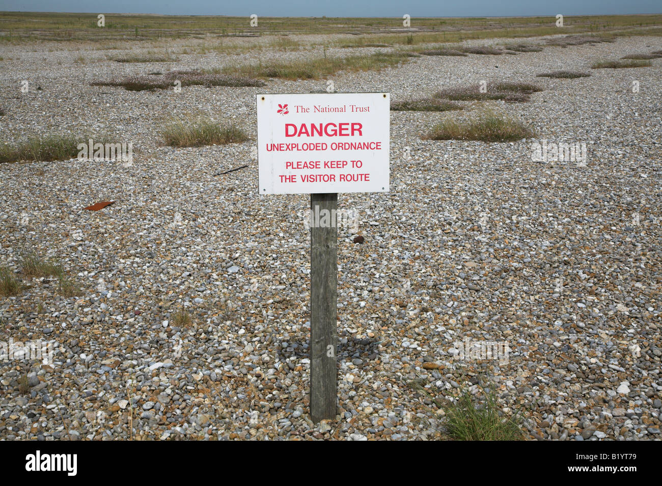 Danger unexploded armaments sign in shingle Orford Ness Suffolk England - Stock Image