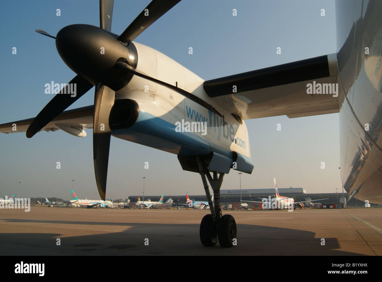 A Flybe Dash8 400 Turboprop aircraft mainly showing the Pratt and Whitney engine viewed from below and looking upwards - Stock Image